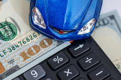Toy car and calculator over dollar Royalty Free Stock Photography