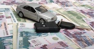 Toy car and car keys. The toy car and car keys against denominations Stock Photos