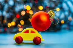 Toy car carries a Christmas tree red ball. royalty free stock images