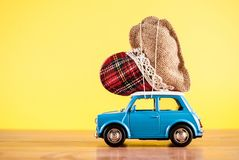 Toy car carrying heart on yellow background royalty free stock photo