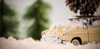 Toy car carrying pine cone on fake snow Stock Photos