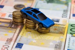 Toy car on coin and euro bills Stock Photo