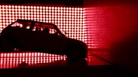 Toy car crashing into wall. Crash test lab concept. Red lights background, super slow motion video