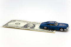 Toy car and a dollar. Blue toy car over 1 dollar bill Royalty Free Stock Photos