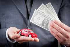 Toy car and dollars in the hands of business man concept for insurance, buying, renting, fuel or service and repair costs Royalty Free Stock Image