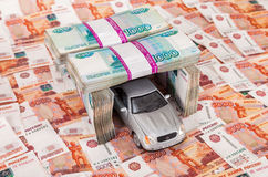 Toy car in the garage of the bundles of money Stock Image