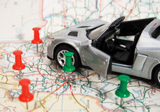 Toy car on a geographical atlas. A toy car is on the road map. convertible silver Royalty Free Stock Photo