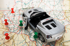 Toy car on a geographical atlas. A toy car is on the road map. convertible silver Stock Photography
