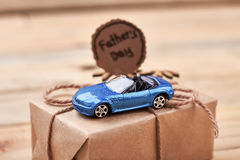 Toy car on gift box. Father`s Day card and bow. Speed of life Stock Photo