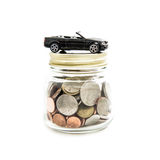 Toy car on the glass jar full of money coins Stock Image