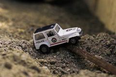 A toy car goes around the sand. A re-enactment where a toy car SUV rides along the sand Royalty Free Stock Photography