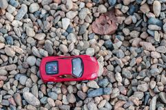 Toy car on gravel. Red modern toy car on gravel. Shallow depth of field Stock Photo