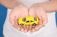 Toy car in hand. A yellow toy car in woman hand Royalty Free Stock Photo