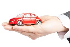 Toy car in the hand of business man concept for insurance, buying, renting, fuel or service and repair costs royalty free stock image