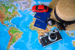 Toy car with hat passport and old camera on map Stock Photos