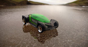 Toy car on iced water. Green toy car on iced water towards horizon stock photo