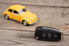 Toy car and key with remote alarm control on the wooden desk Royalty Free Stock Images