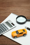 Toy car, magnifying glass, calculator, pen and notebook. Royalty Free Stock Photography