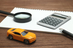Toy car, magnifying glass, calculator, pen and notebook. Stock Photos