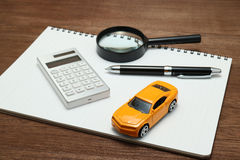 Toy car, magnifying glass, calculator, pen and notebook. Royalty Free Stock Photo