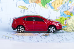 Toy Car on Map. Side view of red, toy, small car on colorful map Stock Photo
