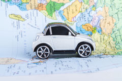 Toy Car on Map. Side view of red, toy, small car on colorful map Stock Photos