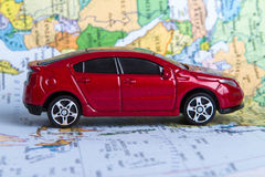 Toy Car on Map. Side view of red, toy, small car on colorful map Stock Images