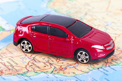 Toy Car on Map. Side view of red, toy, small car on colorful map Royalty Free Stock Photo