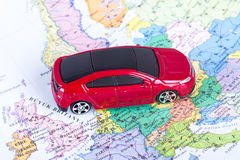 Toy Car on Map. Top view of red, toy, small car on colorful map Royalty Free Stock Photo