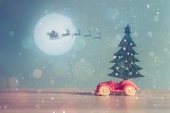Toy Car med julgran- och gåvaasken Jul landskap med gåvor och snöar Hälsningbil för glad jul och för lyckligt nytt år Royaltyfri Fotografi