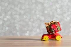 Toy Car med julgran- och gåvaasken Jul landskap med gåvor och snöar Hälsningbil för glad jul och för lyckligt nytt år Royaltyfri Bild