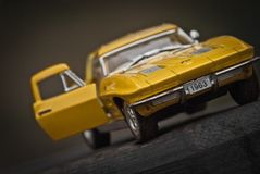 Toy car model Corvette Sting Ray 1963 year. Yellow color. Front view. Opened door. Close-up. Macro. stock images