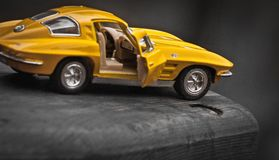 Toy car model Corvette Sting Ray 1963 year. Yellow color. Side view. Opened door. Close-up. Macro. royalty free stock photography