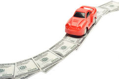 Toy car moving on a US paper currency road Royalty Free Stock Photos