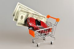 Toy car with money in shopping cart on gray royalty free stock photography