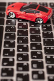 Toy car over laptop keyboard Royalty Free Stock Images