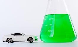 Toy Car Parked branco na frente da garrafa de Erlenmeyer enchida com o líquido verde Foto de Stock Royalty Free