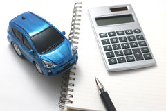 Toy car, pen, calculator, and notebook Stock Image