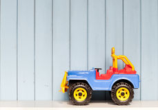 Toy car. Plastic toy car jeep on the bookshelf in children's room on blue wooden background Stock Photo