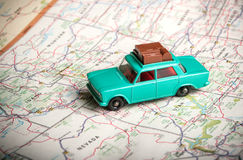 Toy car on a road map. Vintage toy car with luggage on the roof with a road map of the U. S royalty free stock photos