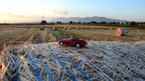 Toy car on a round straw bale stock footage