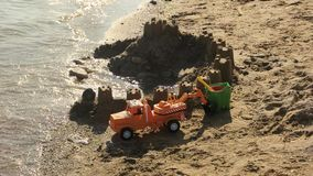 Toy car and sandcastle. Toys on the shore. True pearl of architecture stock video footage