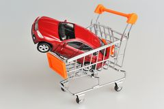 Toy car in shopping cart on gray Royalty Free Stock Images