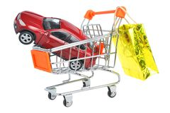 Toy car in shopping cart with hanging gold package isolated on w Stock Photography