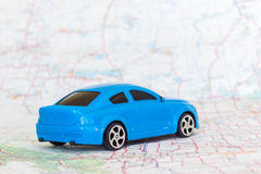Toy car sitting on road map. Little blue toy car sitting on road map Stock Photos