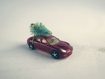 Toy car with a small Christmas tree on the roof Stock Photos
