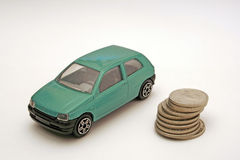 Toy car and a stack of coins. A picture of an old green toy car, next to a stack of coins on a white surface Royalty Free Stock Photography