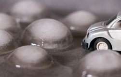 Toy car surrounded by ice cubes. Driving for bad weather concept royalty free stock images