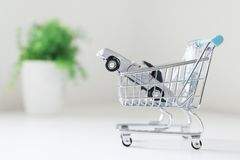 Toy car in toy shopping trolley,. Closeup of a toy car in the basket of a toy shopping trolley with a blurred green plant in a white pot as part of the gray stock photos