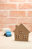 Toy car truck and house in front of brick wall. Royalty Free Stock Photography